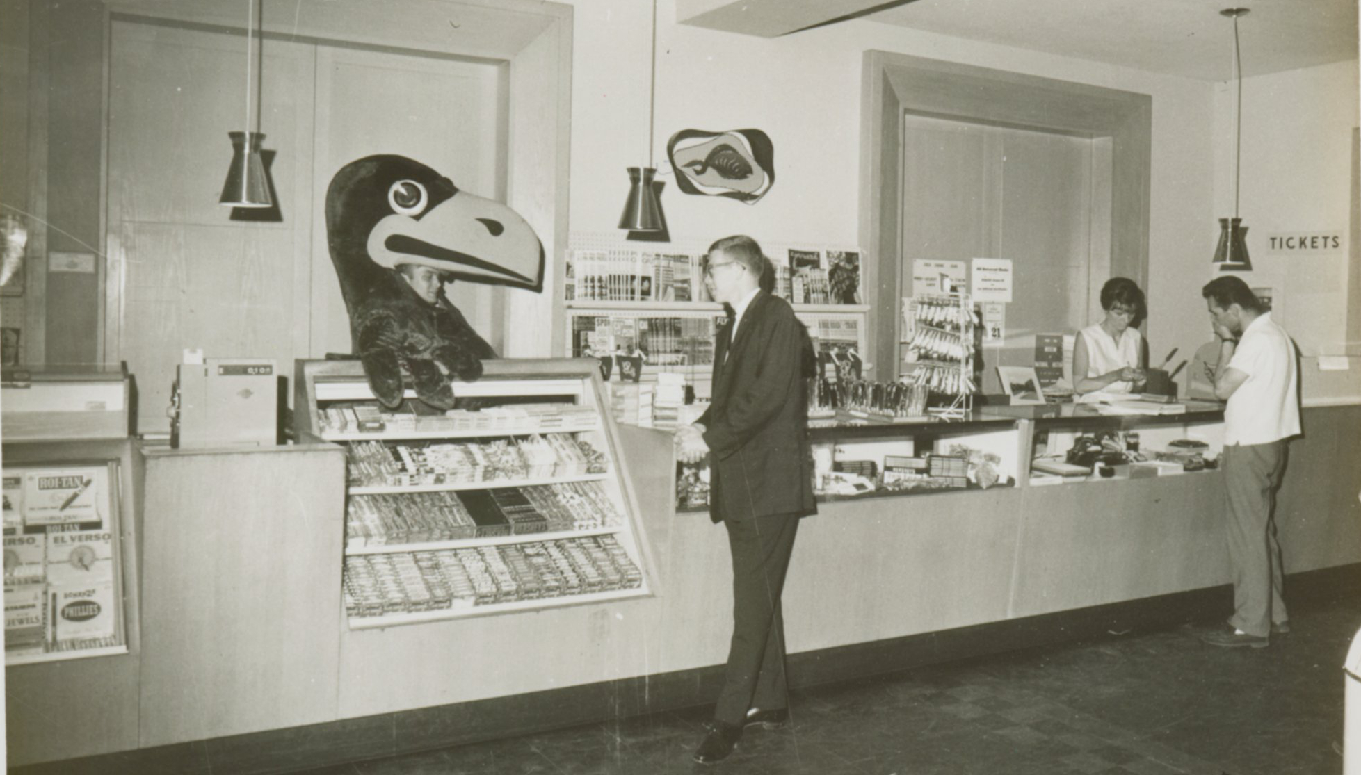 Jayhawk mascot hanging out behind the counter in the Union bookstore, 1963-1964.
